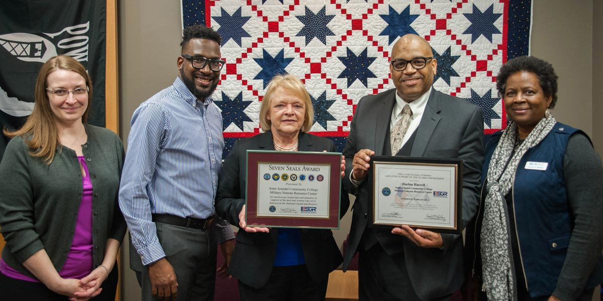 Harlan Harrell receives award for support of military students.