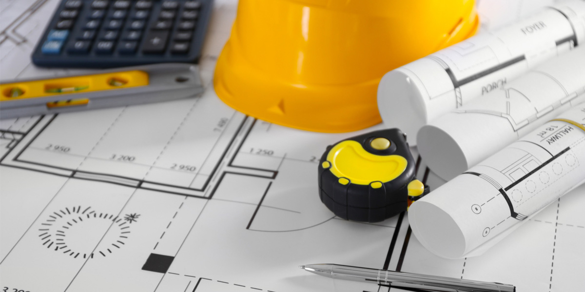 Blueprints, tape measure, hard hat and other tools on a table.