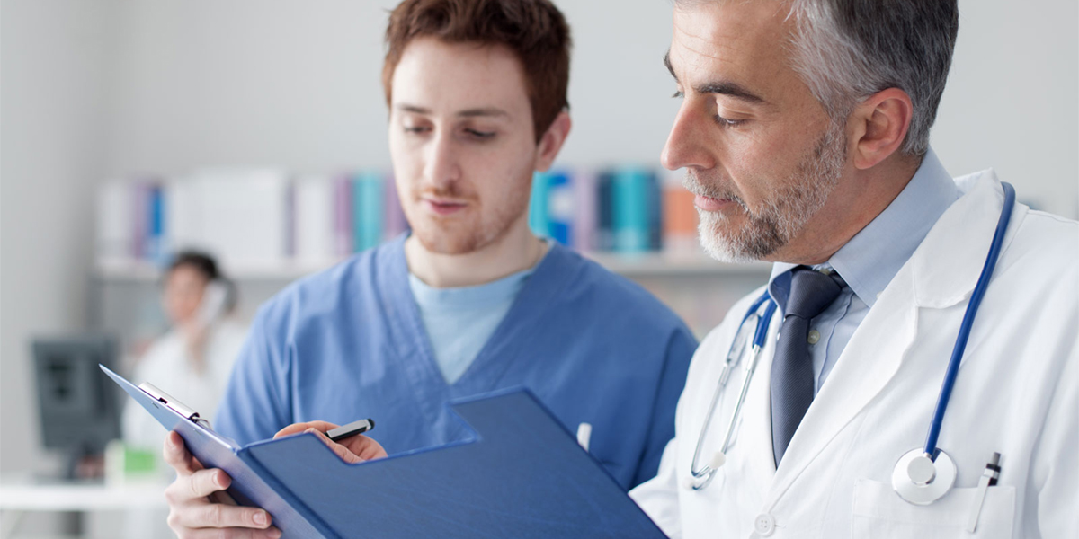 physician assistant with doctor looking at patient record