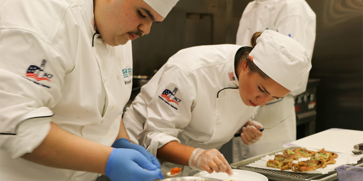 Two HCAT students work on their dishes for the Atlantic Cup.