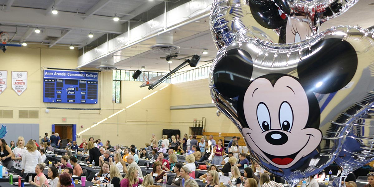 Mickey balloon with workshop attendees in the background.