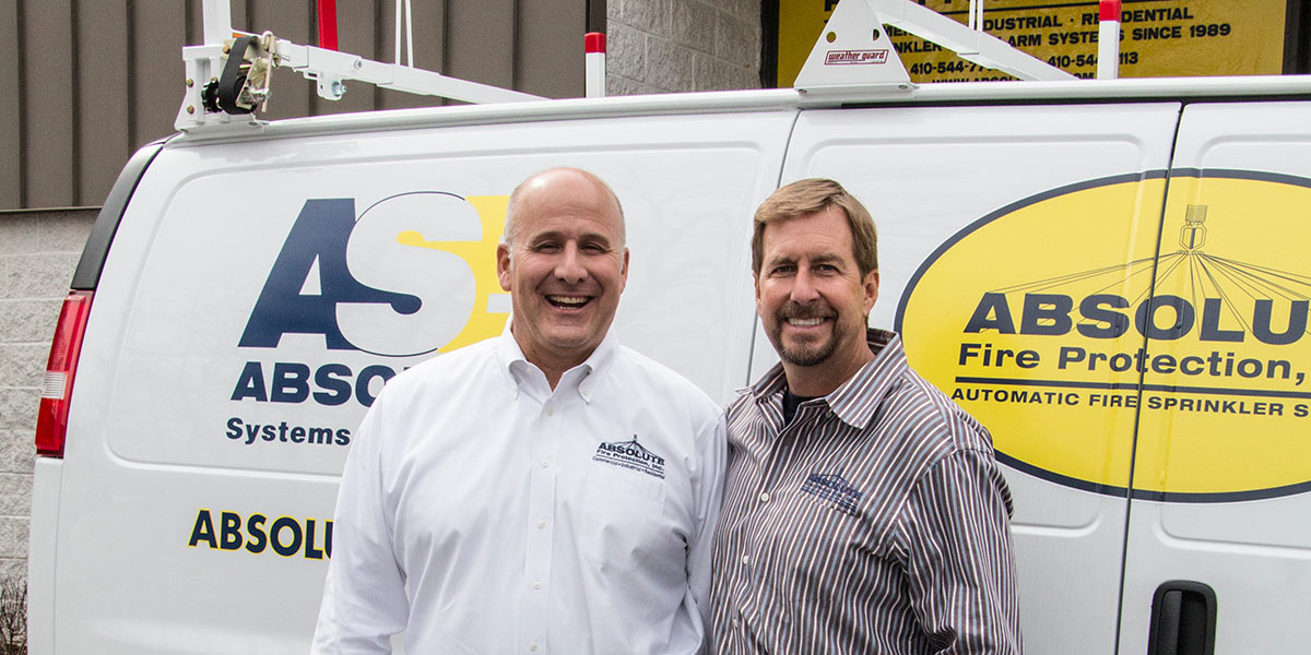 Larry Cate and Dan Mathias in front of Absolute Fire Protection van.