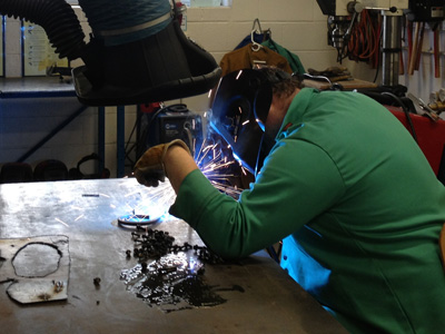 AACC student works with metal.