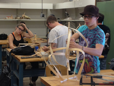 AACC art students work with wood.
