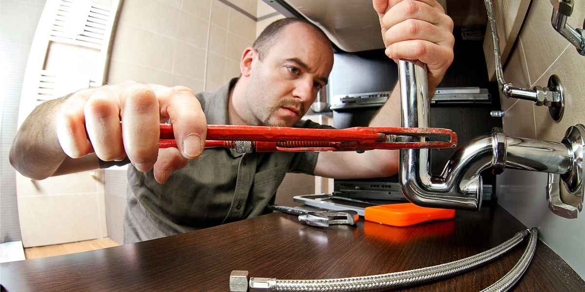 plumbing apprentice with wrench