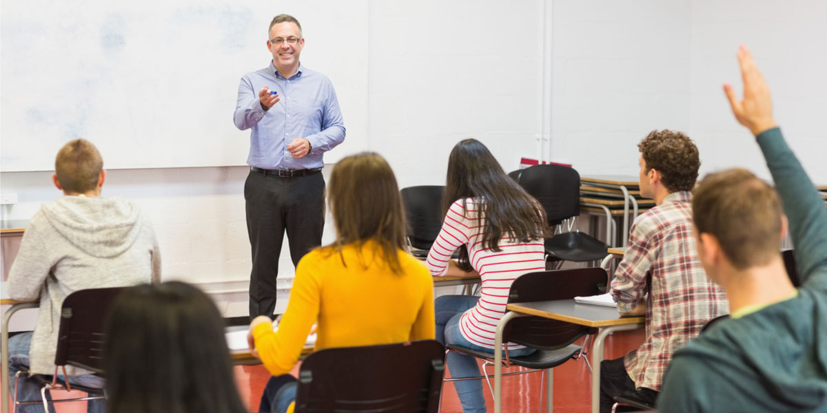 Male teacher stands in front of classroom.