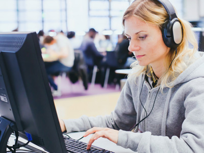 woman at computer with headphones