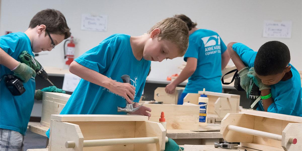 Kids in college building with woodworking tools.